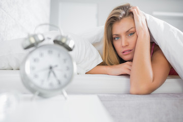 Exhausted blonde looking at camera with alarm clock in foregroun