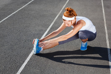 Female runner stretching before workout.