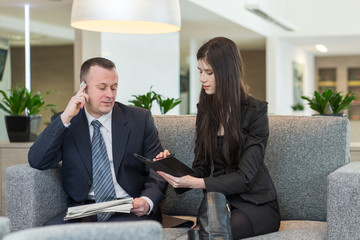 man with phone and women talking about business