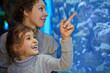 Little girl admiringly shows her mother something in aquarium
