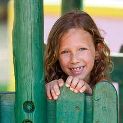 Portrait of cute girl at wooden fence.