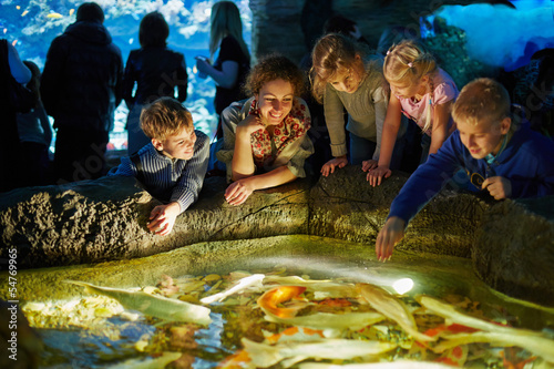 Young woman and several children see after fishes