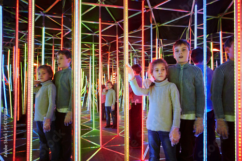 Boy and his sister wander in semidarkness of mirror labyrinth