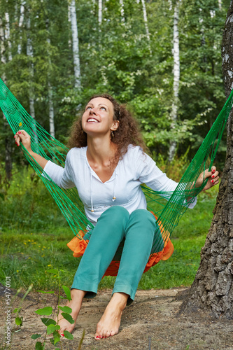 Young smiling woman with yellow flower in hand sits in hammock