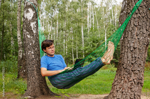 Young barefooted man in glasses with reclines in hammock