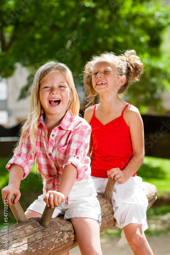Two girl friends having great time in playground.