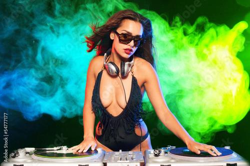 Beautiful DJ girl on decks on the party,