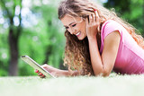 Woman lying on grass with digital tablet