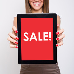 Beautiful young woman showing tablet screen that states sale