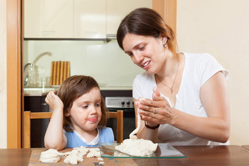 A girl with her mother learns to mold dough figurines in home