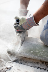man sawing stone with grinder