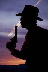 Cowboy silhouette blow end of pistol