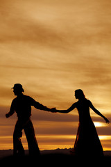 Cowboy reaching back for womans hand silhouette
