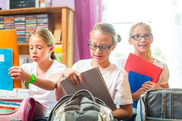 Mädchen packen Ranzen für Schule