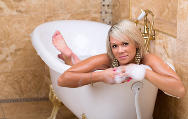 Beautiful tanned girl is taking a luxurious bath