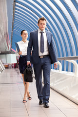 businessman and businesswoman walk