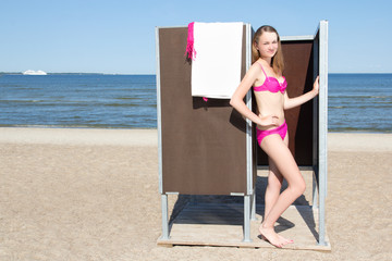 slim beautiful woman in changing cabin on the beach