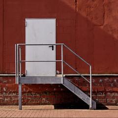 Rote Backsteinwand fassade mit Treppe und Schatten