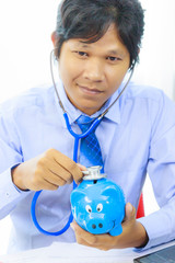 business man with stethoscope checking piggy bank , financial di