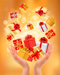 Holiday background with hands holding gift boxes. Concept of giv