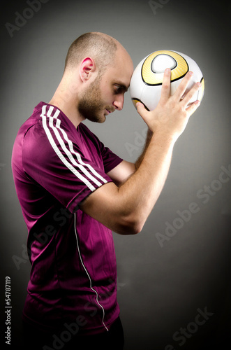 Soccer Player Holding Ball against Head