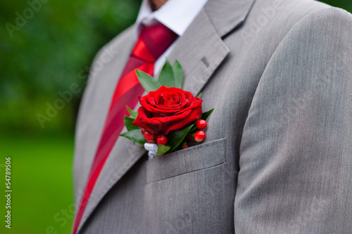 Red boutonniere on gray groom's jacket