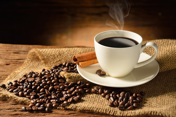 Coffee cup and coffee beans on old wooden background