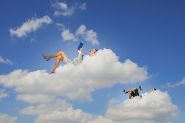 Businesswomen lying on clouds