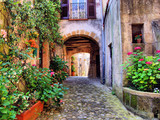 Fototapety Arched cobblestone street in a Tuscan village, Italy
