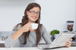 Woman holding a cup of coffee while reading a newspaper