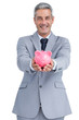 Joyful businessman holding piggy bank