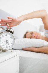 Blonde woman turning off her alarm in the morning