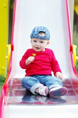 baby on slide wiht dandelion in hand