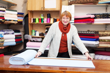 saleswoman measures the fabric