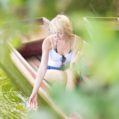Woman relaxing on the vintage wooden boat.