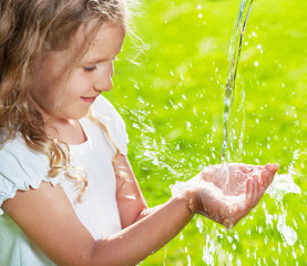 Stream of clean water pouring into children's hands