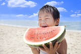 Fototapety 夏の海でスイカを食べる子供