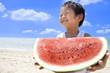 夏の海でスイカを持つ笑顔の子供