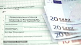 German tax form and Euro money banknotes and coins
