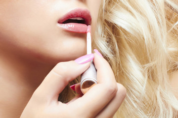 beautiful blond woman paints lips with lipstick.