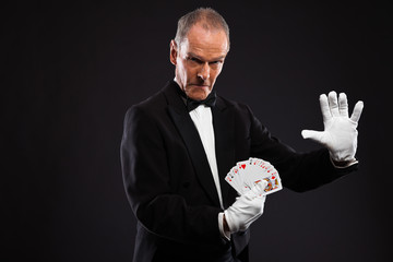 Magician holding cards. Wearing black suit. Studio shot against