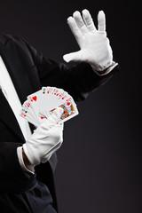 Hands of magician holding cards. Wearing black suit. Studio shot