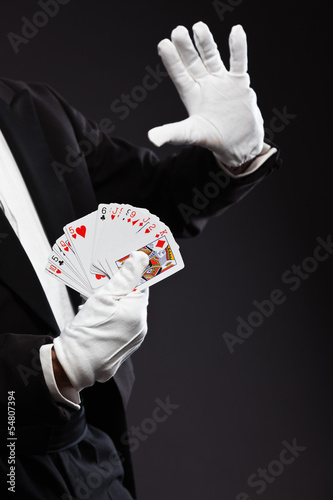 Hands of magician holding cards. Wearing black suit. Studio shot