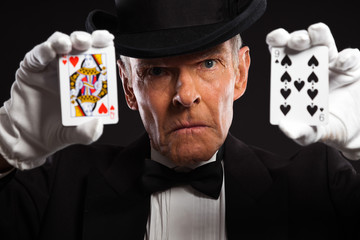 Magician with black suit and hat holding set of cards. Studio sh