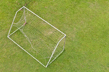 View above the goal nets torn badly beaten in a green grass