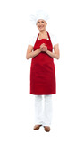 Attractive female chef in red apron and toque