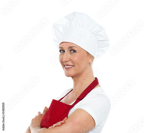 Middle aged confident female chef posing