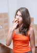 Pretty teen girl eating peach, indoor