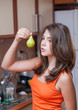 An attractive teen girl holding a pear in her hand