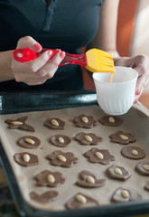Glazing cookies on baking paper in a tray